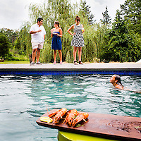 Celebrity Chef Jose Garces joins guests as they dine around the pool, as Garces' daughter Olivia swims, at Jose Garces' country home outside of Philadelphia.<br /> <br /> Scott Lewis for The Wall Street Journal<br /> TOT_POOL