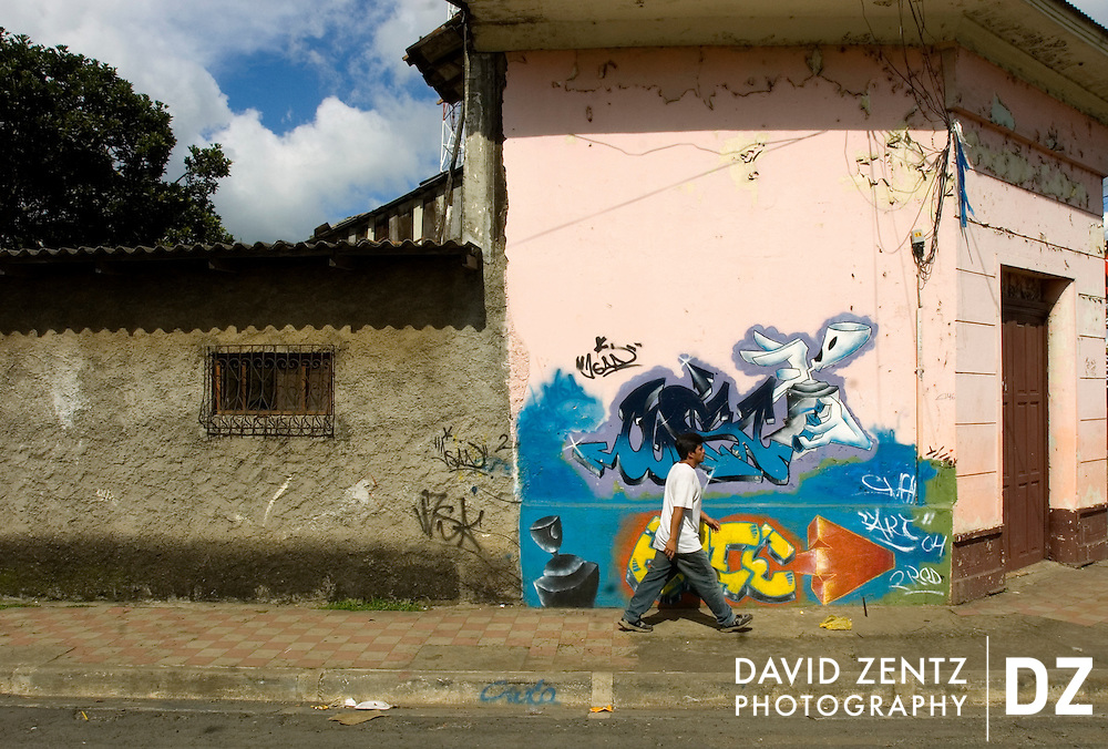 A man walks past a graffiti-covered building in Jinotepe, Nicaragua on October 2, 2004.