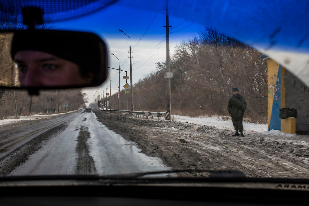 HIRNE, UKRAINE - DECEMBER 8, 2014: A man in military clothing stands at a bus stop along the road between Donetsk and Luhansk in Hirne, Ukraine. CREDIT: Brendan Hoffman for The New York Times