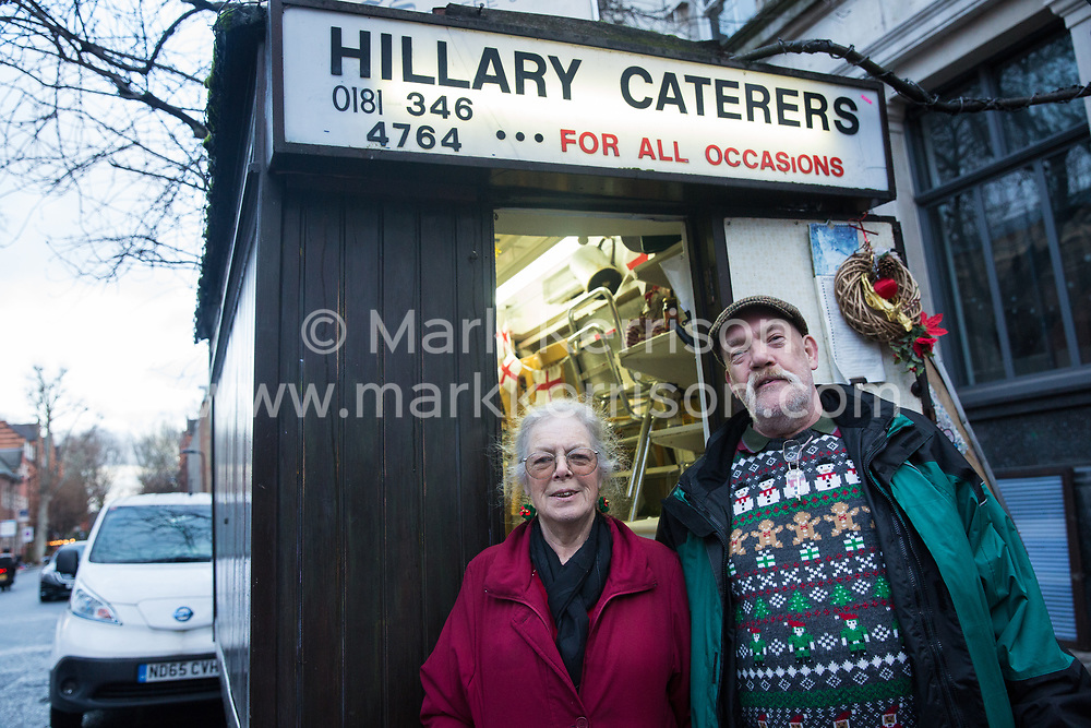 London, UK. 20 December, 2019. Jane Tothill and Syd Tothill Junior, grandchildren of Syd Tothill, pose in front of Syd's Coffee Stall, which has been run by three generations of the same family on the corner of Shoreditch High Street and Calvert Avenue since 1919, immediately before it was closed for business. The mahogany coffee stall, which has been run by Jane Tothill for thirty years, will go on display in the new Museum of London in Smithfield in 2024.