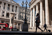 Londoners sit in and walk through Bank Triangle, with the Bank of England on the left and Royal Exchange on the right, in the City of London, UK.