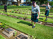 "11 NOVEMBER 2018 - KANCHANABURI, KANCHANABURI, THAILAND:  Scottish veterans of the British army look for the headstones of Scottish soldiers buried in Kanchanaburi War Cemetery during the Rememberance Day ceremony in Kanchanaburi, Thailand. Kanchanaburi is the location of the infamous ""Bridge On the River Kwai"" and was known for the ""Death Railway"" built by Japan during World War II using allied, principally British, Australian and Dutch, prisoners of war as slave labor. There are 6,982 people buried in the cemetery, including 5,000 Commonwealth soldiers and 1,800 Dutch soldiers. November 11, 2018 marked the 100th anniversary of the end of World War I, celebrated as Rememberance Day in the UK and the Commonwealth and Veterans' Day in the US.     PHOTO BY JACK KURTZ"