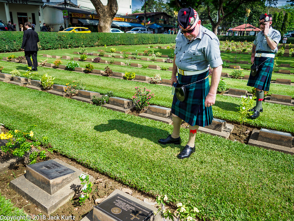 """11 NOVEMBER 2018 - KANCHANABURI, KANCHANABURI, THAILAND:  Scottish veterans of the British army look for the headstones of Scottish soldiers buried in Kanchanaburi War Cemetery during the Rememberance Day ceremony in Kanchanaburi, Thailand. Kanchanaburi is the location of the infamous """"Bridge On the River Kwai"""" and was known for the """"Death Railway"""" built by Japan during World War II using allied, principally British, Australian and Dutch, prisoners of war as slave labor. There are 6,982 people buried in the cemetery, including 5,000 Commonwealth soldiers and 1,800 Dutch soldiers. November 11, 2018 marked the 100th anniversary of the end of World War I, celebrated as Rememberance Day in the UK and the Commonwealth and Veterans' Day in the US.     PHOTO BY JACK KURTZ"""