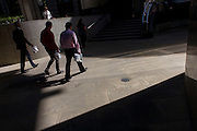 Three associates walk through area of City of London sunlight with takeaway lunch bags.