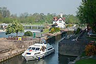 Cruiser exiting the lock on the River Thames at Goring, Oxfordshire, Uk
