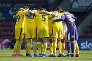 Wimbledon players huddle before kick off during the EFL Sky Bet League 1 match between Scunthorpe United and AFC Wimbledon at Glanford Park, Scunthorpe, England on 30 March 2019.