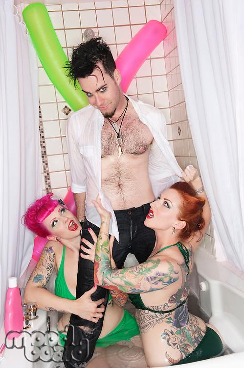 Man standing in bathtub with women seducing him