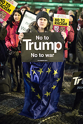 """© Licensed to London News Pictures . 20/02/2017 . Manchester , UK . Woman wearing a European Union flag and holding a """" No to Trump """" poster . Hundreds of protesters at a Stop Trump demonstration in Albert Square , central Manchester , to coincide with Parliament debating a petition calling for the government to cancel a State Visit by US President Donald Trump . Photo credit: Joel Goodman/LNP"""