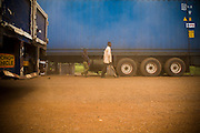 People are engulfed by a cloud of dust as they walk past large trucks near Notse, Togo on Thursday October 2, 2008.
