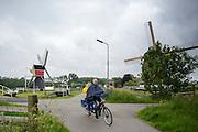 Een stel rijdt op een elektrische tandem in de regen voorbij de twee poldermolens bij Oud-Zuilen. Bij Utrecht wordt de tandemtocht gehouden. De tocht werd van 1975 tot 1982 jaarlijks gehouden en was in die tijd een groots succes. Organisator Herbert Kuner, een expert in oude fietsen, wil het nu nieuw leven inblazen. In totaal rijden dit jaar vijftien tandems mee. Tijdens de route van 40km rondom Utrecht hoeven de fietsers slechts zes verkeerslichten te passeren.<br /> <br /> A couple on a electric bike pass the two mills near Oud-Zuilen. In Utrecht, the tandem tour is held. The tour was held annually from 1975 to 1982 and at that time was a grand success. Organizer Herbert Kuner, an expert in old bikes, wants to restart the tradition. In total this season, with fifteen tandems. During the route of 40km around and Utrecht cyclists passing only six traffic lights.