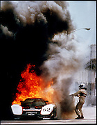 A race car driver attempts to put out a fire in his car during a race.