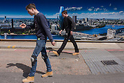 Two men walk past a large construction hoarding that shows 1, Blackfriars, a property development marketing suite hoarding landscape. 1 Blackfriars or One Blackfriars, will be a mixed-use development approved for construction at the junction of Blackfriars Road and Stamford Street at Bankside, London. The development make make up a 52-storey tower of a maximum height of 170m and two smaller buildings of 6 and 4 stories respectively. Uses include residential flats, a hotel and retail. In addition a new public space will be created.