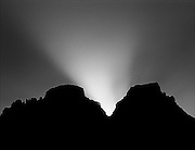 Sunset silhouette of the Horns, Drakensberg, South Africa.  Crepuscular rays (God beams) diffracting at the neck between Inner Horn 3005m / 9858ft (left) and Outer Horn 3006m / 9860ft (right).  The saw-tooth profile of tiny peaks to the left is a group called The Chessmen.  Inner Horn was first climbed in 1925; Outer Horn in 1934.  The names are believed to have been derived from the Zulu name for nearby Cathedral Peak.  However, under some lighting conditions, as seen here, the gap between the Horns resembles antlers or deer horns.  One of the last free ranges of the San people or Bushmen, the Drakensberg is steeped in San folk lore.  Nikon F100, 70-300/4-5.6D, Kodak E100VS.