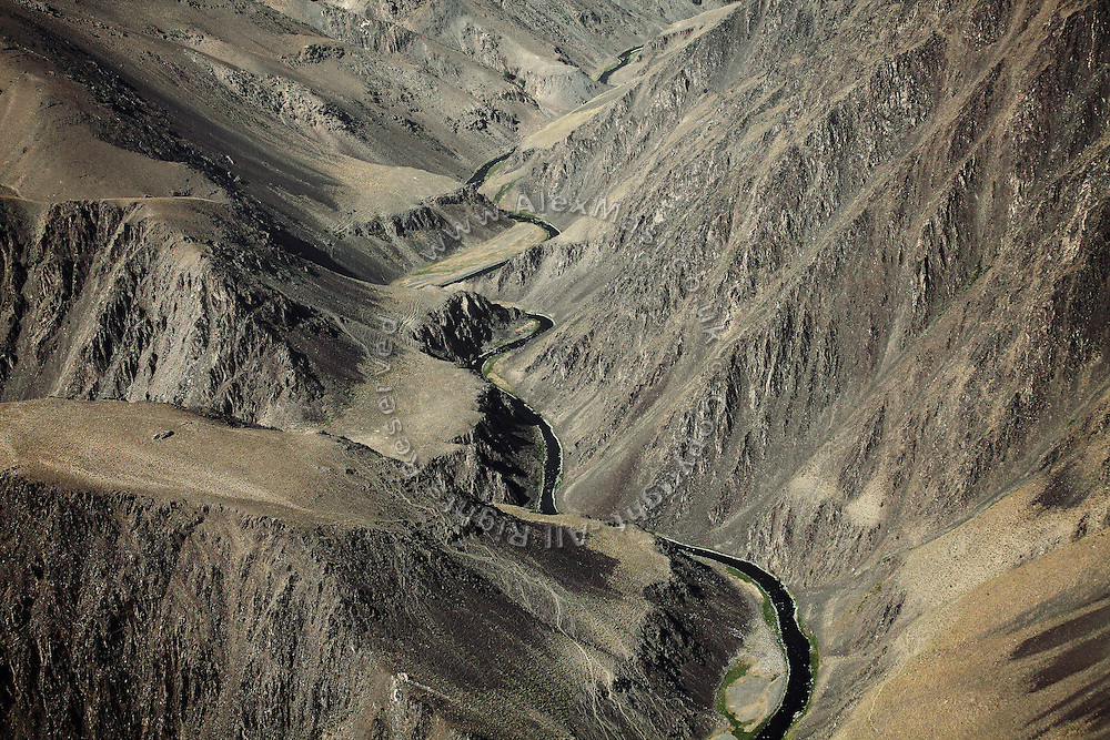 A river running through the Hindu Kush, the mountain range crossing Afghanistan and separating Kabul from Bamiyan, is photographed from a UNAMA helicopter on its way to the capital. The Buddhas of Bamiyan were two 6th century monumental statues of standing Buddhas carved into the side of a cliff in the Bamiyan valley in the Hazarajat region of central Afghanistan, situated 230 km northwest of Kabul at an altitude of 2500 meters. The statues represented the classic blended style of Gandhara art. The main bodies were hewn directly from the sandstone cliffs, but details were modelled in mud mixed with straw, coated with stucco. Amid widespread international condemnation, the smaller statues (55 and 39 meters respectively) were intentionally dynamited and destroyed in 2001 by the Taliban because they believed them to be un-Islamic idols. Once a stopping point along the Silk Road between China and the Middle East, researchers think Bamiyan was the site of monasteries housing as many as 5,000 monks during its peak as a Buddhist centre in the 6th and 7th centuries. It is now a UNESCO Heritage Site since 2003. Archaeologists from various countries across the world have been engaged in preservation, general maintenance around the site and renovation. Professor Tarzi, a notable An Afghan-born archaeologist from France, and a teacher in Strasbourg University, has been searching for a legendary 300m Sleeping Buddha statue in various sites between the original standing ones, as documented in the old account of a renowned Chinese scholar, Xuanzang, visiting the area in the 7th century. Professor Tarzi worked on projects to restore the other Bamiyan Buddhas in the late 1970s and has spent most of his career researching the existence of the missing giant Buddha in the valley.