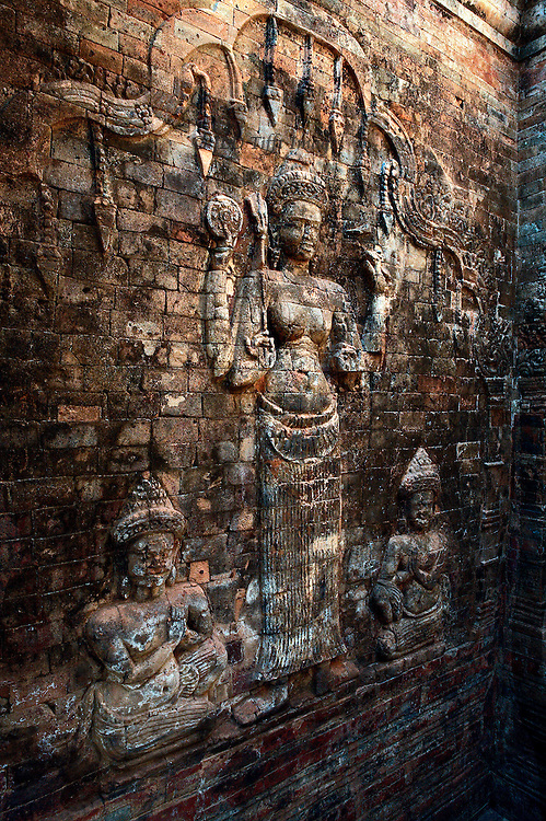 Angkor: Prasat Kravan (10th century): interior brick wall relief of Lakshmi holding her attributes, with kneeling worshippers.  Seen from the side, from the entrance doorway.