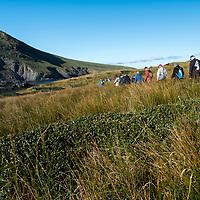 National Geographic/Lindblad Expeditions guests walk through the landscape surrounding Franklin Bay on Isla de los Estados, Argentina.