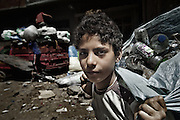 "Young plastic bottles collector in Mokattam. Classification of different types of plastic in Mokattam.The quarry was originally located where the settlement of Mokattam, is now used for storage of paper and aluminum.On the outskirts of Cairo in the middle of Manshiet Nasr neighborhood is located Mokattam settlement known as ""Garbage City"" is inhabited by Zabbaleen, a community of about 45,000 Coptic Christians living for decades to recycle waste generated by the Egyptian capital: plastic, aluminum, paper and organic waste transformed into compost. Most part of the Association for the Protection of the Environment (APE), an NGO that works in the area, whose objectives are to protect the environment and improve the livelihoods of garbage scavengers in Cairo. According to the UN, the work is done in Mokattam is one of the ten best examples of world environmental improvement. El Cairo , Egypt, June 2011. ( Photo by  Jordi Camí )."
