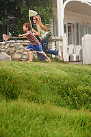 Brother and sister (5-6 10-12) holding fishing nets running in front of house