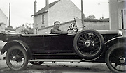man posing in his big car in a rural little village 1920s