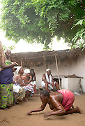 "Shrine servant possessed by spirits during a ""coming out"" ceremony at a fetish shrine in Aflao, Volta Region, Eastern Ghana. A woman was released after spending three months in a small, dark room, hoping that she'd then be able to find a husband. Despite most Ghanaians being adamant followers of christianism or islam, many of them still maintain traditional beliefs. When facing a problem of any nature, some people will visit a local fetish shrine, looking for help. The main priest will consult the oracles and tell the person in need what has to be done for the problem to go away. People will typically be asked to ""serve"" the shrine for weeks, sometimes months, as their families pay the priest for their upkeep."