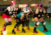 "October 17, 2010 - Lancaster, MA - Maureen ""Cat O'Mighty"" Reddington-Wilde (left) and Dawna ""Lady Bugher"" Norum (right) of the Brawlin' Broads prepare to block the jammer (center) of Granite State Roller Derby. The jammer is the skater with the star on her helmet, she scores points by passing members of the opposing team. (Photos/Matt Wright 2010)"