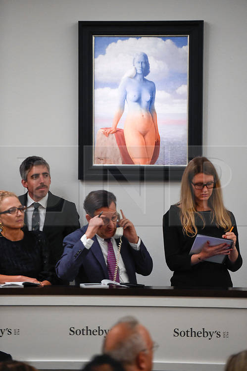 © Licensed to London News Pictures. 19/06/2019. LONDON, UK. Sales staff in front of ''La Magie Noire'' by René Magritte, (Est. £2,500,000 - 3,500,000) which sold for a hammer price of £3,500,000 at Sotheby's Impressionist & Modern art evening sale in New Bond Street. This is the first major evening sale to take place after Sotheby's agreed to a takeover by media and telecoms billionaire Patrick Drahi in a deal valued at $3.7bn (£2.9bn).  The big five global auction houses (Sotheby's, Christie's, Bonhams, Phillips and China Guardian Auctions) will now be held privately.  Francois Pinault, another French billionaire, owns Sotheby's traditional rival Christie's.   Photo credit: Stephen Chung/LNP