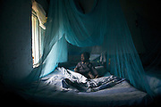 A boy is safely tucked in under a mosquito net. ..Mosquito nets save lives