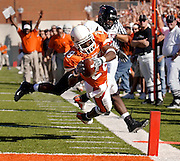 Oklahoma State wide receiver Tommy Devereaux dives for the end zone to score past Texas Tech defensive back Tim Norman in Stillwater, OK.