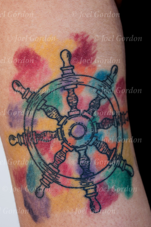 Tattoo of ship's wheel tattoo on her arm.<br /> <br /> Tattoos are no longer just a male thing, young women are just as likely to get a tattoo as males. <br /> <br /> Body art or tattoos has entered the mainstream it is no longer considered a weird kind of subculture.<br /> <br /> &quot;According to a 2006 Pew survey, 40% of Americans between the ages of 26 and 40 have been tattooed&quot;.