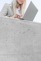 Mid section of young businesswoman using laptop on terrace