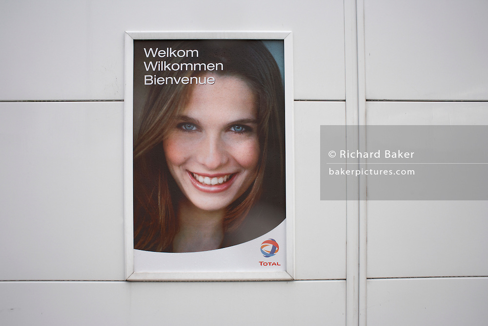 A young model's smiling face on a Total petrol advert welcomes visitors to a truck stop wall in southern Belgium