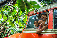 Matagalpa, Nicaragua, May 2014. Boys play in an old bus. We overnight at a homestay in La Corona village. The people own, or work in, small familiy coffee plantations that sell their Arabica coffee via Sol Cafe, a Fair Trade cooperative. Matagalpa tours offers trips to coffee plantations and remote villages, rural community tourism, agro-tourism, hiking and biking. Central America's largest and least populated country consists of lakes; volcanoes and Spanish colonial cities. Photo by Frits Meyst / MeystPhoto.com