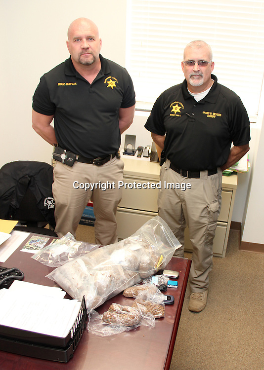 (Floyd Ingram / Buy at photos.chickasawjournal.com)<br /> Jail Warden Brand Huffman, left, and Chickasaw County Sheriff James Meyers stand behind a desk covered with tobacco and cell phone nabbed in an alleged smuggling attempt to get the contraband to inmates.