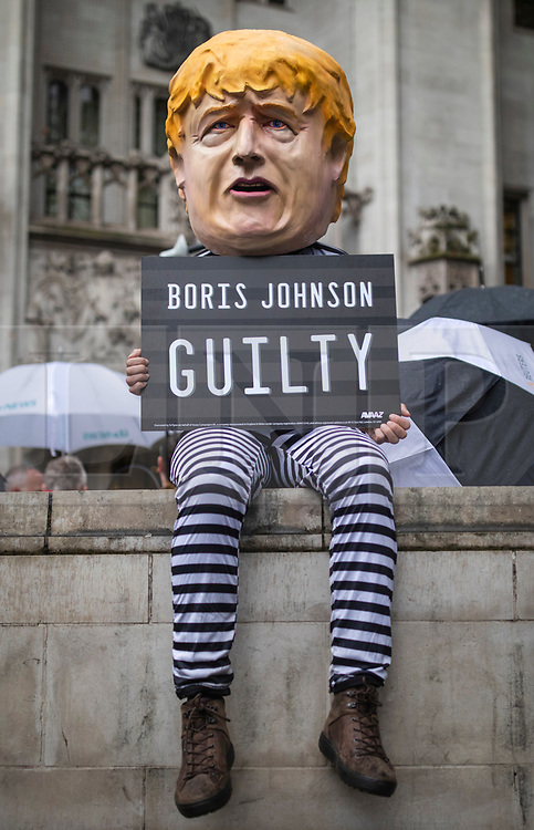 © Licensed to London News Pictures. 24/09/2019. London, UK. A protester wearing a Boris Johnson head sits outside the Supreme Court in London after judges ruled that Prime Minister Boris Johnson's suspension of Parliament was unlawful. Photo credit: Rob Pinney/LNP