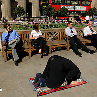 Muslim prayers while others enjoy lunchtime sunshine in the city, by the Bank of England.