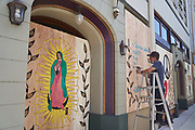 Redwood City artist Roberto Cruz paints murals on boarded up business windows after days of protests and looting in the San Francisco Bay Area, photographed in Redwood City, California, on June 2, 2020. (Stan Olszewski for ZUMA Press)