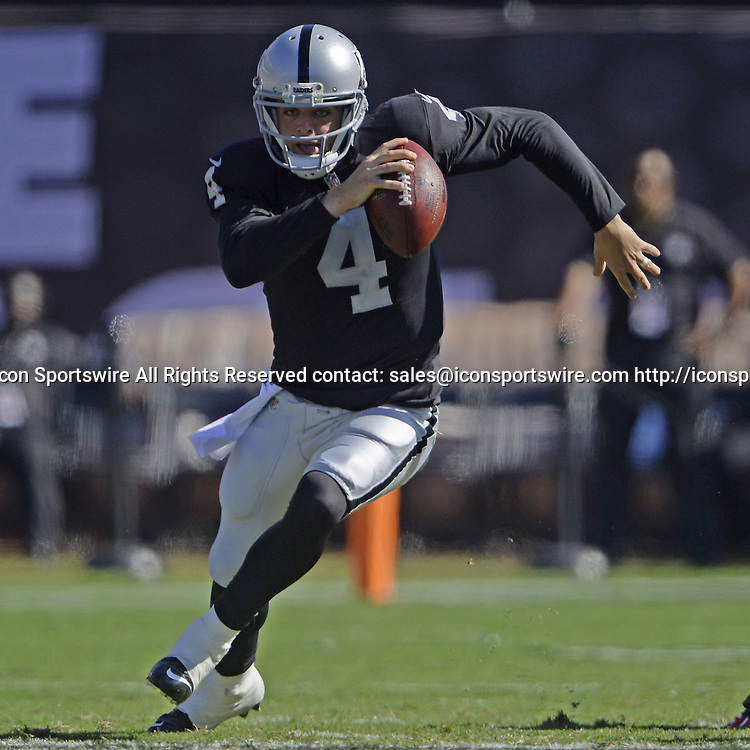 Oct. 19, 2014 - Oakland, CA, USA - Oakland Raiders quarterback Derek Carr (4) runs with the ball before being tripped up by Arizona Cardinals defensive end Kareem Martin (96) during the second quarter on Sunday, Oct. 19, 2014, at O.co Coliseum in Oakland, Calif