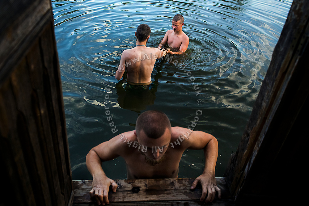 After strenuous physical training, a young man (top right) participating to the ultra-nationalistic Azovets children's camp is washing his clothes alongside two instructors, while standing in a water pond near the village of Buzova, 30 km west of Kiev, the capital of Ukraine.