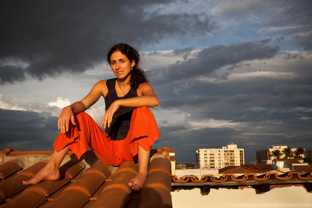 A young Brazilian woman sits barefoot on a rooftop at sunset in Brasilia, Brazil.