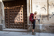 Pilgrim on Camino Santiago de Compostella checking map on route by doorway in Santo Domingo de la Calzada in  La Rioja, Spain