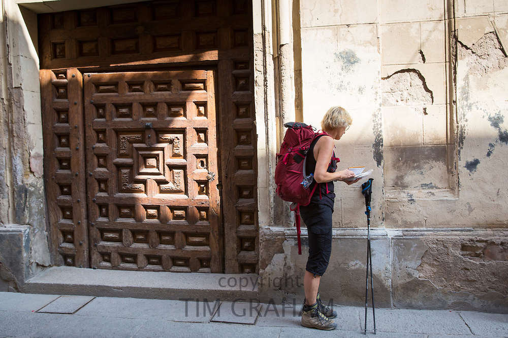 Pilgrim on Camino Santiago de Compostella checking map on route by doorway in Santo Domingo de la Calzada in  La Rioja, Spain