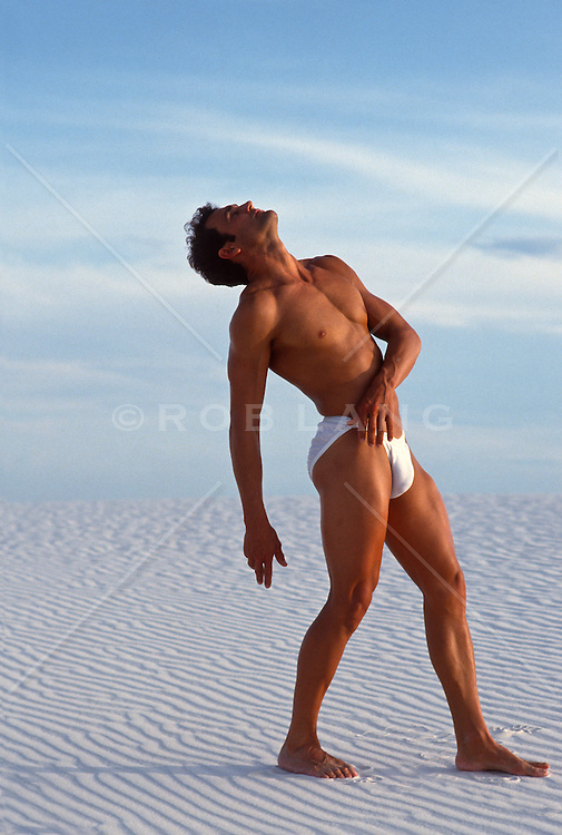 Toned man in white briefs posing on the white sand in White Sands National Park, New Mexico