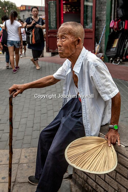 2011 08 10 Beijing China Peking Kina<br /> Gammal man med k&auml;pp och solfj&auml;der i centrala Beijing<br /> <br /> <br /> ----<br /> FOTO : JOACHIM NYWALL KOD 0708840825_1<br /> COPYRIGHT JOACHIM NYWALL<br /> <br /> ***BETALBILD***<br /> Redovisas till <br /> NYWALL MEDIA AB<br /> Strandgatan 30<br /> 461 31 Trollh&auml;ttan<br /> Prislista enl BLF , om inget annat avtalas.