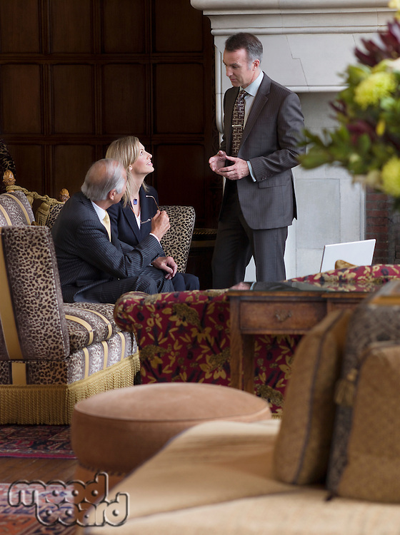 Three business people talking in lobby sofas in foreground