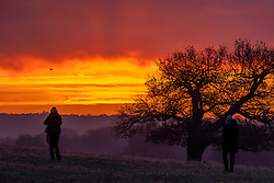 © Licensed to London News Pictures. 05/12/2019. London, UK. A walker captures the rising sun this morning in a frosty and misty Richmond Park as weather forecasters predict warmer weather for the South East. Photo credit: Alex Lentati/LNP