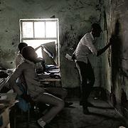 Un professeur enseigne les mathématiques à des écoliers dans une salle de classe endommagée par les combats, à Malakal. Trois écoles ont rouvert dans cette ville à la rentrée, en février 2017, après trois années de fermeture. Les autorités tentent de faire revenir la population en assurant des services élémentaires.