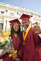 Two graduates holding diploma and flowers outside university portrait