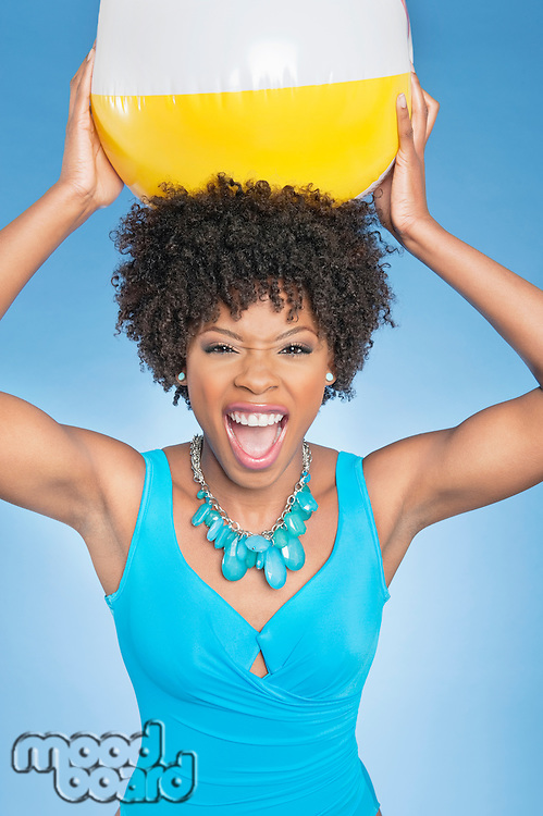 Attractive African American woman holding beach ball aloft over colored background