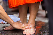 "12 JULY 2014 - PHRA PHUTTHABAT, SARABURI, THAILAND: People wash monks' feet to make merit during the Tak Bat Dok Mai at Wat Phra Phutthabat in Saraburi province of Thailand. Wat Phra Phutthabat is famous for the way it marks the beginning of Vassa, the three-month annual retreat observed by Theravada monks and nuns. The temple is highly revered in Thailand because it houses a footstep of the Buddha. On the first day of Vassa (or Buddhist Lent) people come to the temple to ""make merit"" and present the monks there with dancing lady ginger flowers, which only bloom in the weeks leading up Vassa. They also present monks with candles and wash their feet. During Vassa, monks and nuns remain inside monasteries and temple grounds, devoting their time to intensive meditation and study. Laypeople support the monks by bringing food, candles and other offerings to temples. Laypeople also often observe Vassa by giving up something, such as smoking or eating meat. For this reason, westerners sometimes call Vassa ""Buddhist Lent.""    PHOTO BY JACK KURTZ"