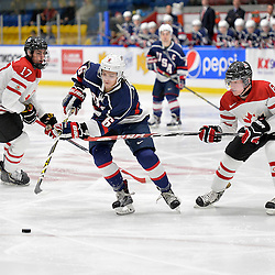 WHITBY, - Dec 18, 2015 -  Game #12 - Bronze Medal Game, Team Canada East vs. United States at the 2015 World Junior A Challenge at the Iroquois Park Recreation Complex, ON. Max Zimmer #6 of Team United States skates with the puck while being pursued by Derek Topatigh #6 of Team Canada East during the first period.<br /> (Photo: Shawn Muir / OJHL Images)